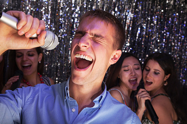 Young man singing into a microphone at karaoke