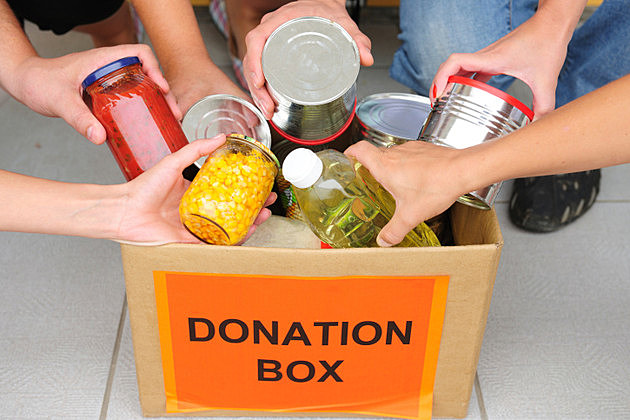 People putting food in a donation box