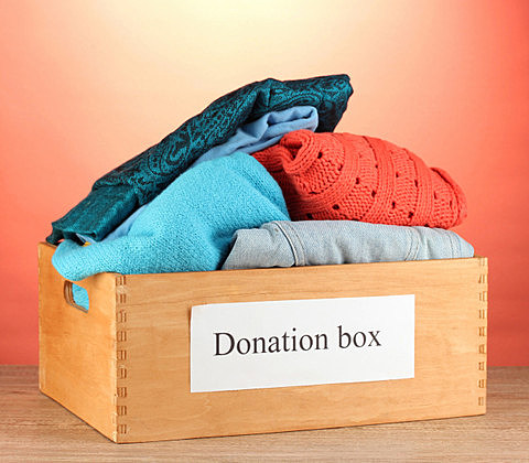 Donation box with clothing on red background close-up